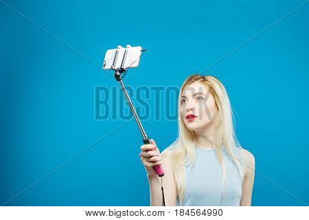 Cute Blonde with Sensual Lips Photographing Herself. Smiling Girl Using Selfie Stick to Take a Photo on Blue Background. Woman Portrait in Studio.