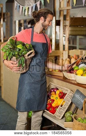 Male staff holding leafy vegetable and using digital tablet in organic section of supermarket