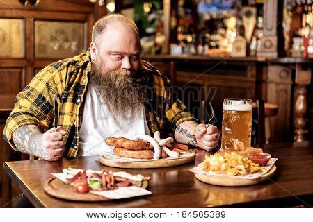 I want eat it all. Fat man expressing astonishment while tasting frankfurters and drinking glass of beer in pub