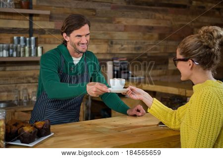 Smiling male barista serving coffee to female customer in cafe