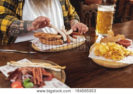 Focus on close up hand of fat man tasting big dish of frankfurters and glass of cold beer in dramshop