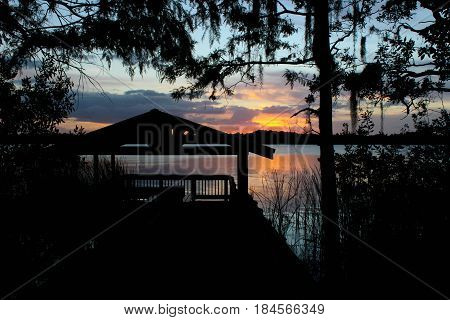 Standing on a boardwalk, looking out towards a pavilion and tree in silhouette that sits on the water's edge, during a sunset afterglow.