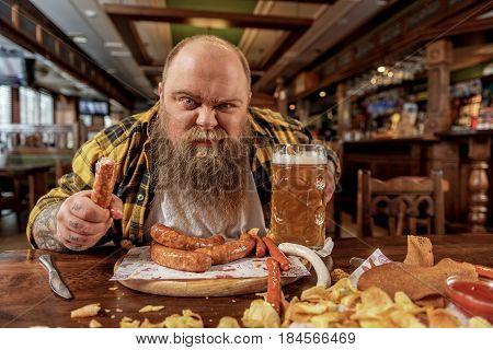 It is my food. Portrait of brute bearded man eating sausages and drinking glass of beer in boozer