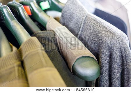 Hunting jackets and clothes hang on shelves in a hunting and fishing store