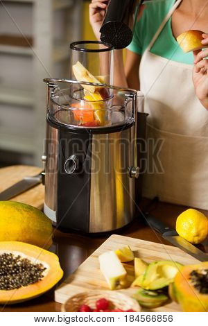 Mid-section of shop assistant preparing juice at health grocery shop