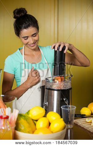 Shop assistant preparing fruit juice at health grocery shop