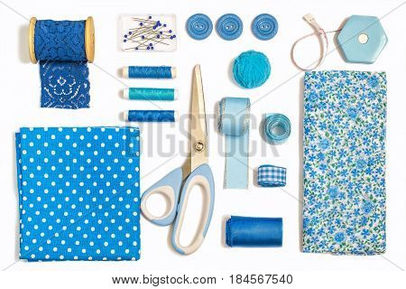 Sewing kit accessories and equipment for sewing blue shades. Various sewing accessories and tools for needlework: fabric threads scissors buttons needles braid ribbons. Flat lay top view