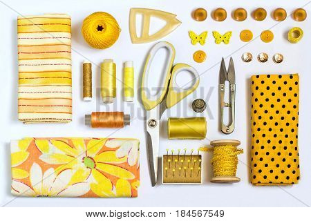 Sewing kit accessories and equipment for sewing yellow shades. Various sewing accessories and tools for needlework: fabric threads scissors buttons needles braid ribbons. Flat lay top view