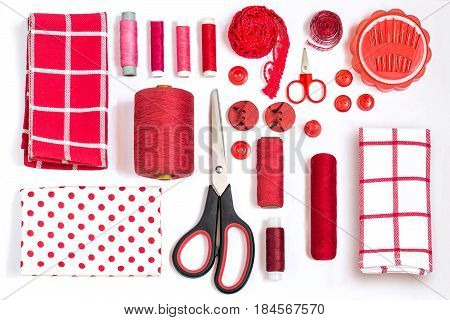 Sewing kit accessories and equipment for sewing red shades. Various sewing accessories and tools for needlework: fabric threads scissors buttons needles braid ribbons. Flat lay top view