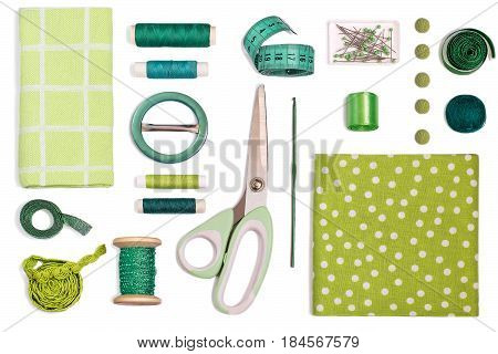 Sewing kit accessories and equipment for sewing green shades. Various sewing accessories and tools for needlework: fabric threads scissors buttons needles braid ribbons. Flat lay top view