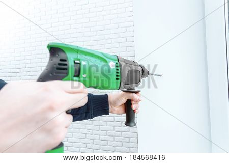 Use hammer drill to drill the wall