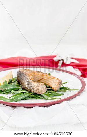 Baked Steak Trout Fish On Green Leaves Of Rucola Lettuce, Lemon,