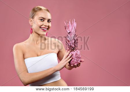 Enjoying fruit. Waist up portrait of smiling young woman holding color pineapple with copy space in right side