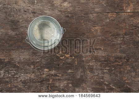 A garden tool, a bucket on a wooden old brown table, close-up. Concept of gardening.