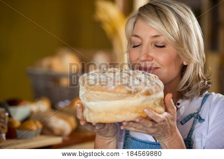 Female staff smelling a sweet food in supermarket