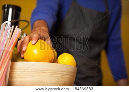 Mid-section of male staff holding lemon fruit at organic section in supermarket