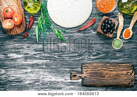 Pizza ingredients - round dough base, fresh tomatoes, sauce, olive oil, green herbs and spices on background of black textured wood. Rustic cutting board as frame. Top view