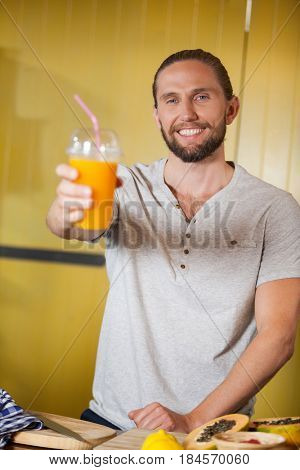 Male staff holding orange juice glass at organic section of supermarket