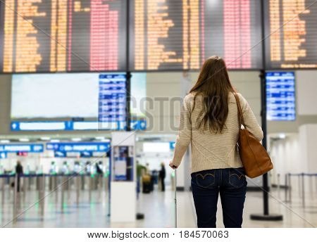 Young woman looking at the flight information board on the airport, checking her flight