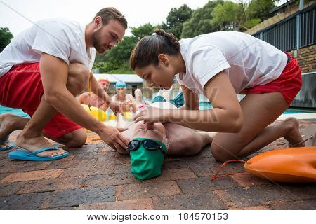 Male and female rescue workers helping unconscious senior man at poolside