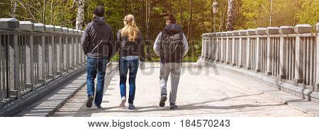 Group of friends walking in the spring park. Banner for website.
