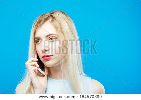 Young Pretty Woman Listen Somebody Using her Smartphone on Blue Background. Cute Girl with Mobile in Studio. Technology Concept.