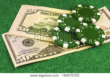 On the green cloth of the poker table is a bill of $ 50 and four green chips