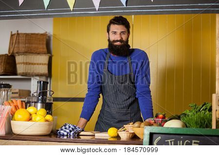 Portrait of male staff standing at organic section in supermarket