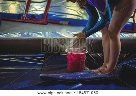 Female gymnast applying chalk powder on her hands before practicing in the gymnasium