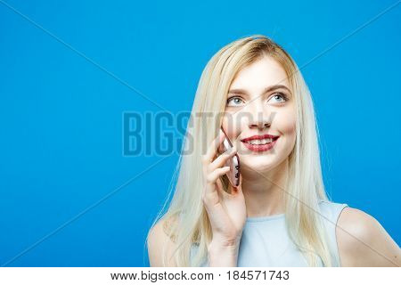 Portrait of Smiling Blonde with Sensual Lips Talking with Somebody by Her Smartphone on Blue Background in Studio. Cute Girl with Mobile.