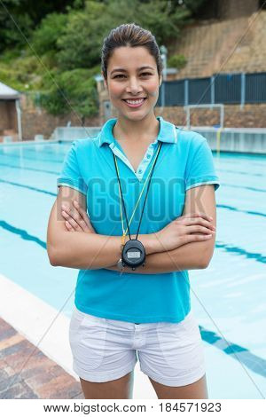 Portrait of smiling female coach standing with arms crossed near poolside