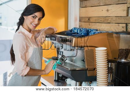 Portrait of waitress cleaning coffeemaker machine in café