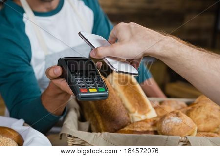 Customer paying bill through smartphone using NFC technology at counter in cafe