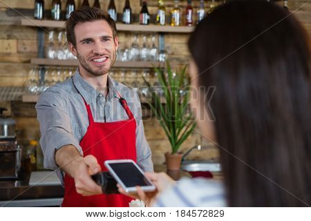 Woman making payment through NFC technology on mobile phone in cafe