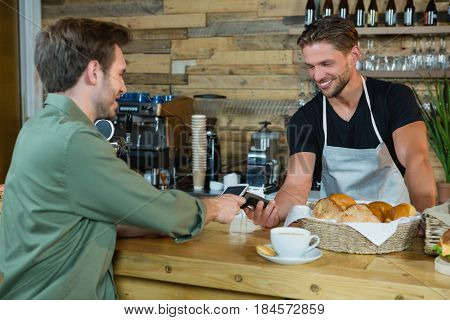 Man making payment through NFC technology on mobile phone in cafe