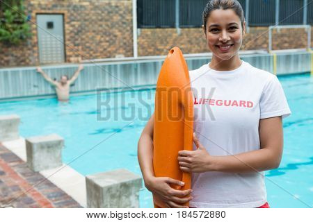 Portrait of lifeguard standing with rescue buoy at poolside
