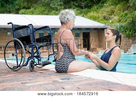Swim coach consoling a disabled senior woman at poolside