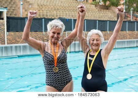 Portrait of excited senior women with gold medals standing at poolside