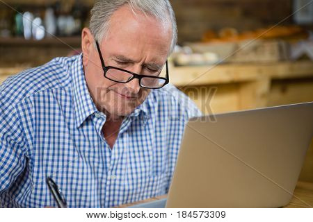 Senior man working on computer in café