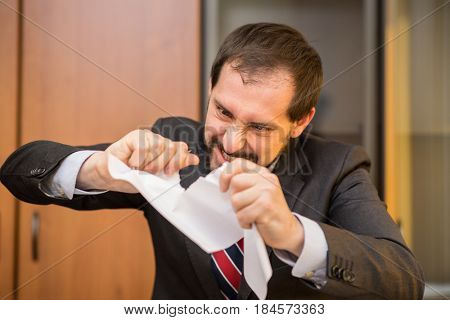 Angry businessman tearing up a document