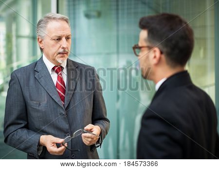 Senior businessman giving advice to a younger colleague