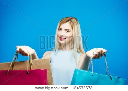 Happy Female Shopper Wearing Dress is Holding Shopping Bags on Blue Background in Studio. Seasonal Sale Concept.