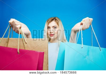 Blonde Female Shopper Wearing Dress is Holding Shopping Bags on Blue Background in Studio. Seasonal Sale Concept.