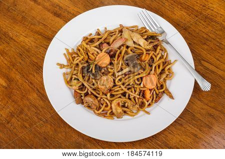 A plate of lo mein noodles with vegetables chicken and shrimp
