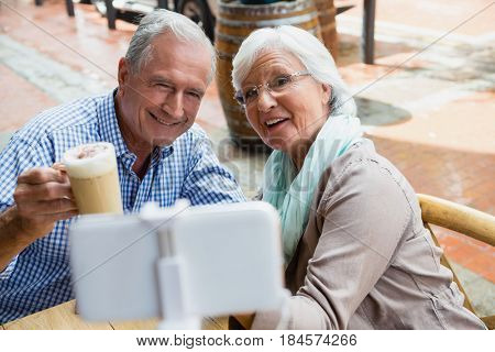 Senior couple taking selfie from mobile phone in outdoor café