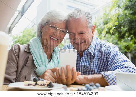 Senior couple using mobile phone in outdoor café