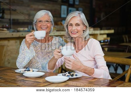 Portrait of senior friends having coffee and breakfast in café