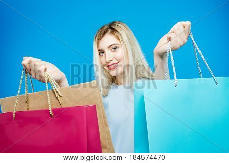 Cute Female Shopper Wearing Dress is Holding Shopping Bags on Blue Background. Happy Girl with Lond Hair and Charming Smile in Studio. Seasonal Sale Concept.