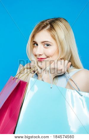 Closeup Portrait of Joyous Female Shopper Wearing Dress is Holding Shopping Bags on Blue Background. Happy Girl with Lond Hair and Charming Smile in Studio. Seasonal Sale Concept.