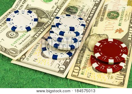On the green cloth of the poker table is one five and ten dollar bills and white and red chips